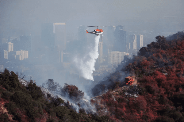 A helicopter drops water on the Getty Fire